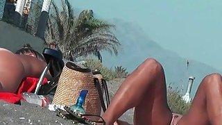 真正的业余裸体主义者与赤裸的阴部在海滩上的辣妹